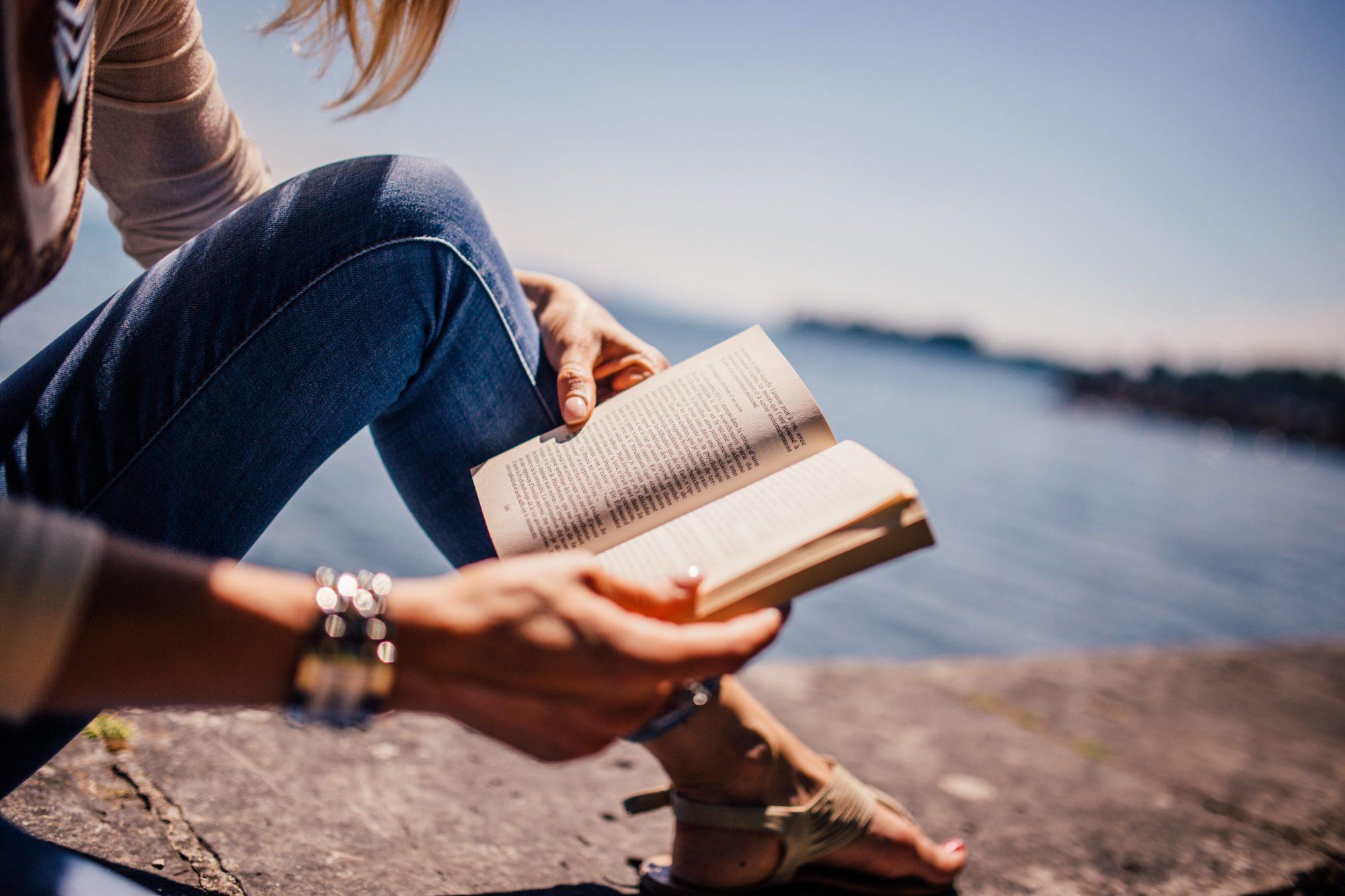 Frau liest entspannt ein Buch am Wasser