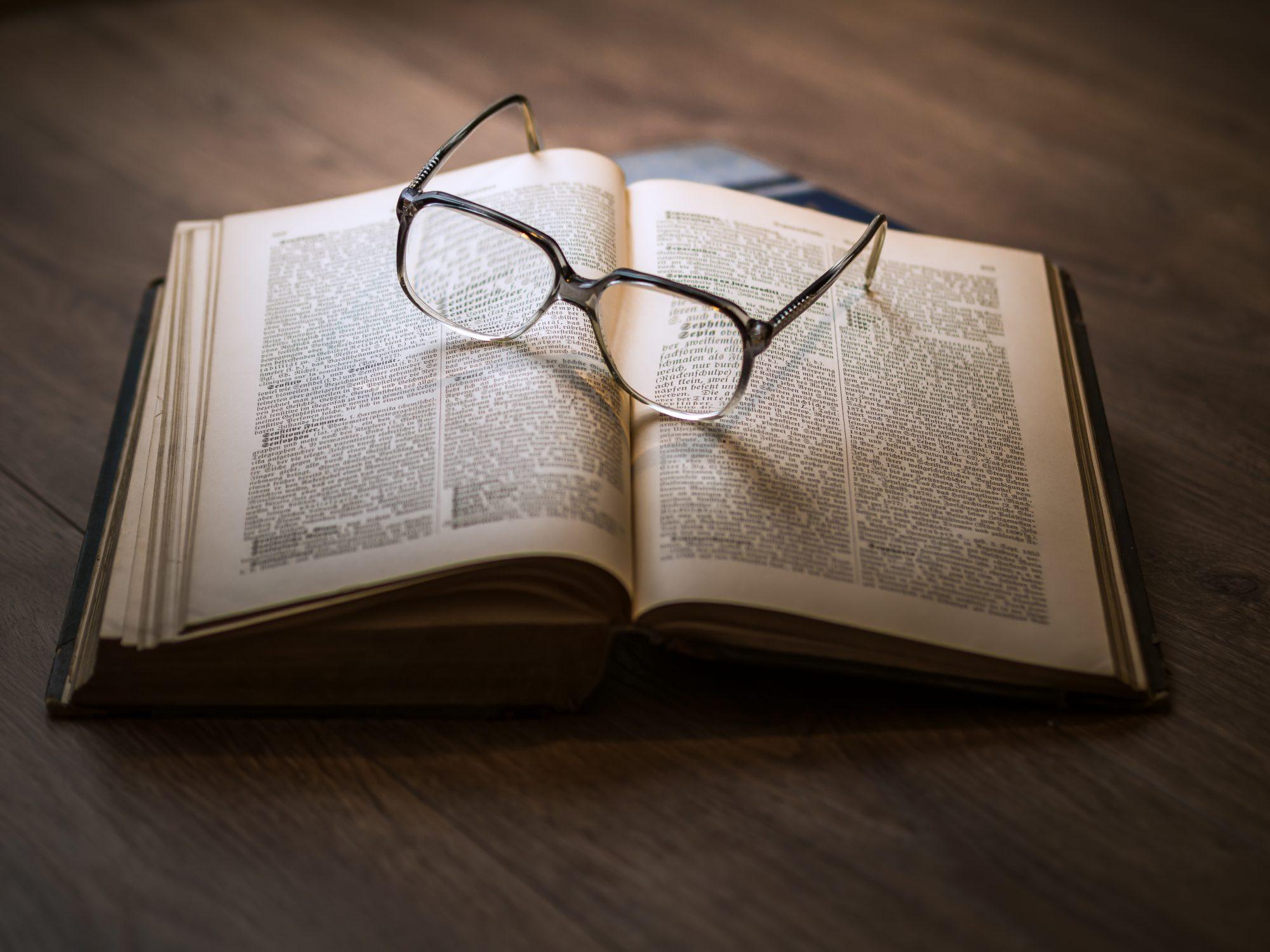 Aufgeschlagenes Buch mit Brille.